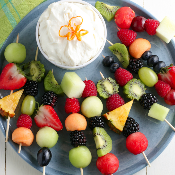 Fruit Kabobs and fruit dip on blue plate for serving