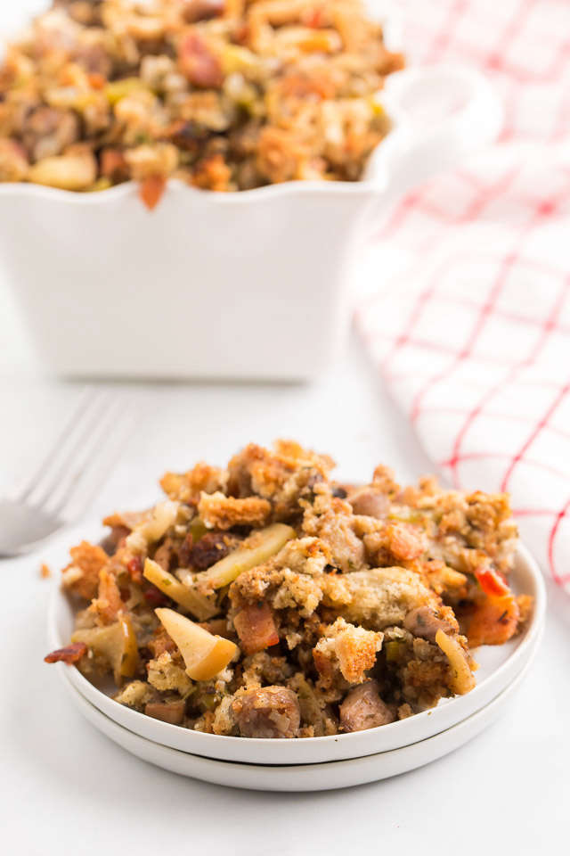 sausage dressing with apples and bacon on white plate and in serving bowl behind it