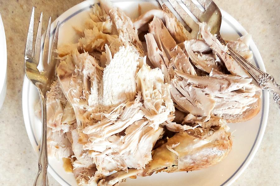 shredded leftover turkey in white dish