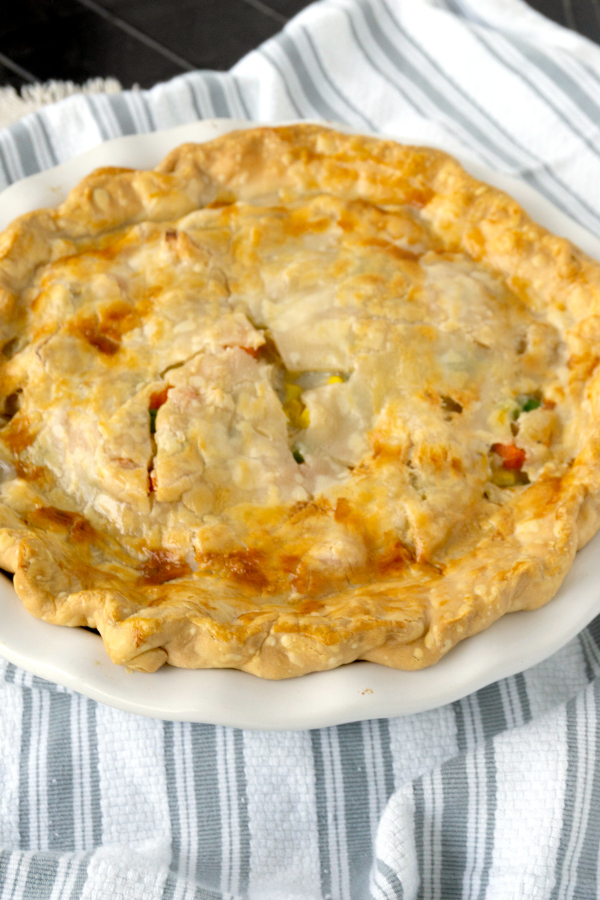 turkey pot pie with pie crust in a white baking dish on a striped towel