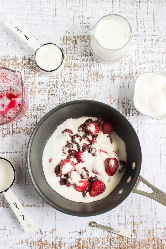 adding half and half to mixed berry puree to make fruit ice cream