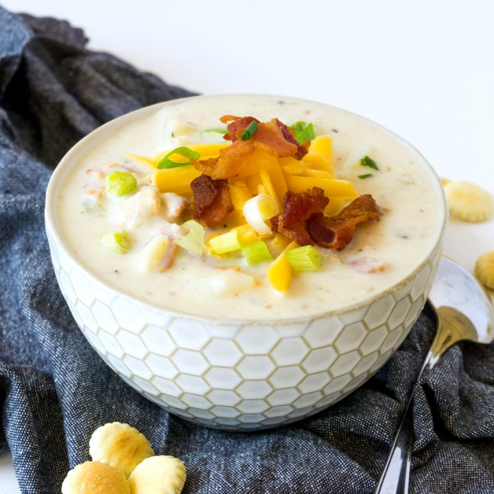 creamy New England clam chowder with bacon and cheese garnish in in white bowl