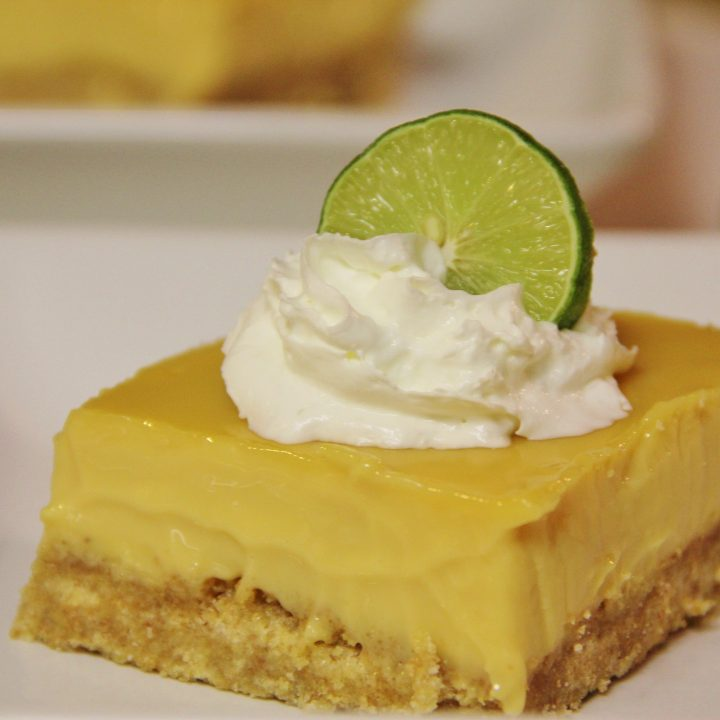 serving of key lime pie topped with whipped cream and lime slice