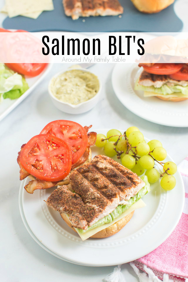 grilled blackened salmon BLT sandwich and green grapes on white plate