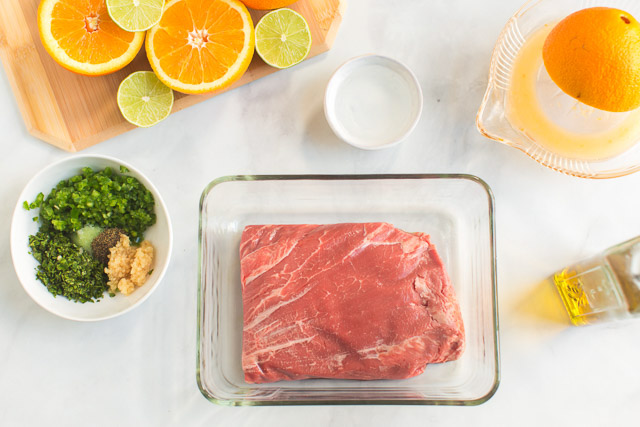 raw flank steak oranges, limes, and seasoning for steak taco recipe