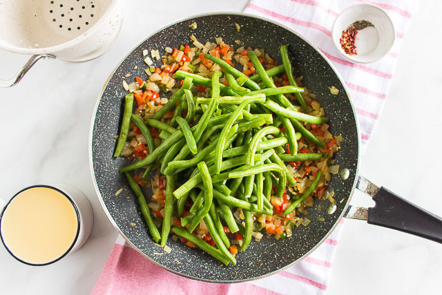 overhead photo: fresh green beans cooking in in a skillet with diced onions and bell peppers