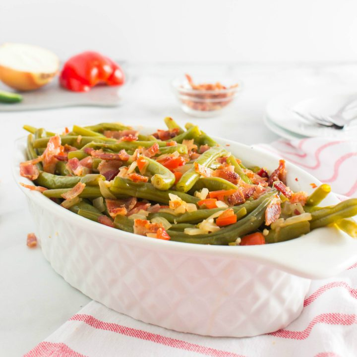 side view: spicy green beans and bacon in white serving dish