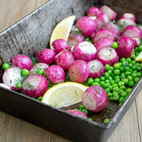 pan of oven-roasted radishes with peas, lemon wedges, and fresh dill