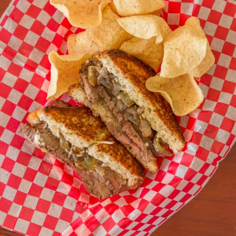 Flank Steak Sandwiches in a basket with potato chips