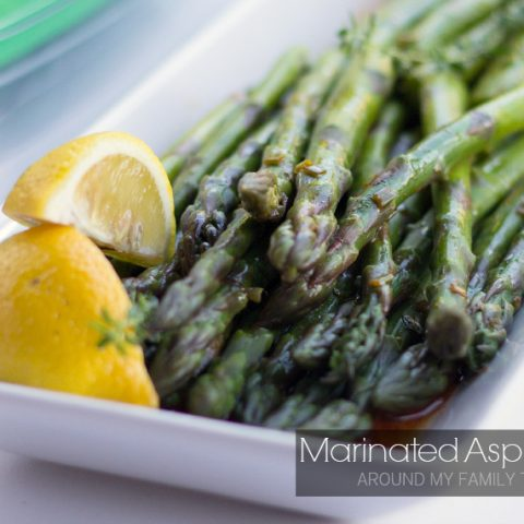 Marinated Asparagus on a platter with lemon wedges