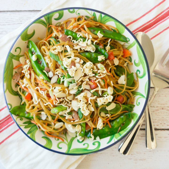 Change up your traditional summer pasta salad for this Spicy Asian Pasta Salad, itwill be the hit of all your summer parties! This pasta salad is full of fresh vegetables and topped with some crushed ramen noodles and slivered almonds. #pastasalad