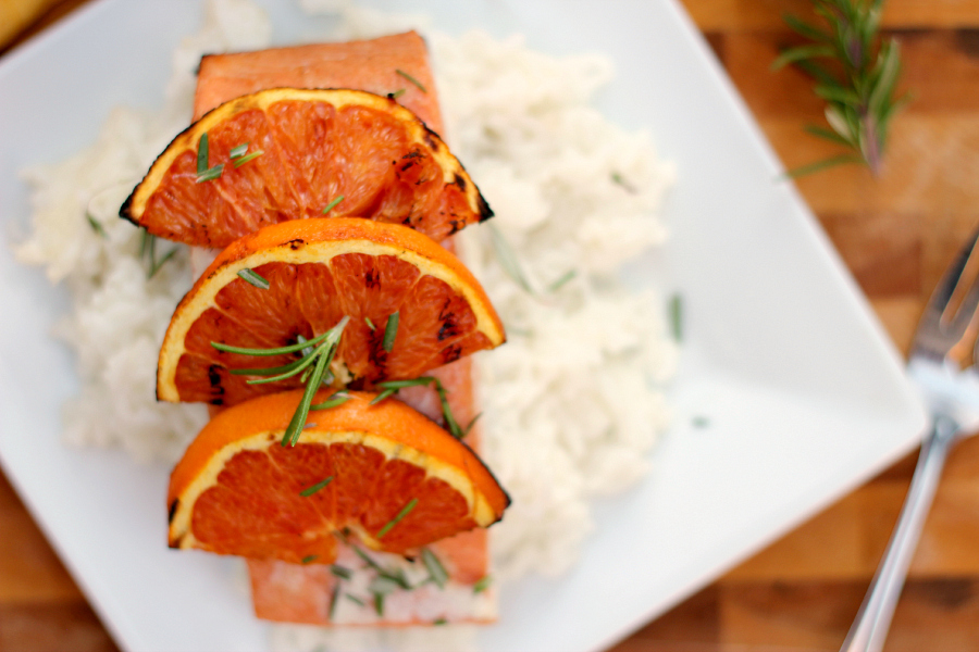 salmon on rice on a white plate with grilled oranges