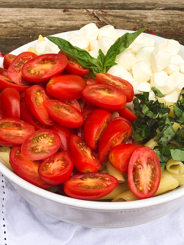 pasta in a white bowl with tomatoes, basil and cheese