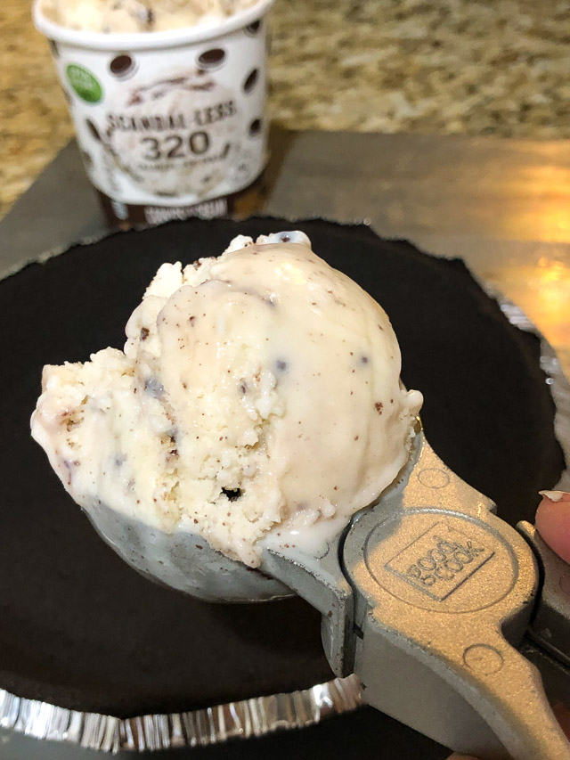 Scoop of ice cream being put into a cookie pie crust