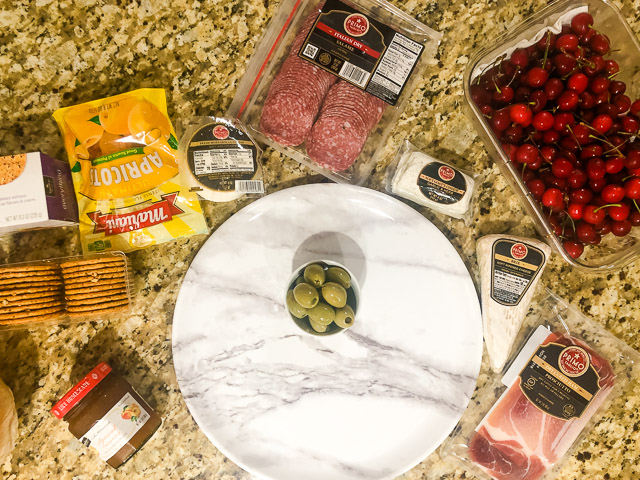 summer charcuterie board ingredients on a granite counter
