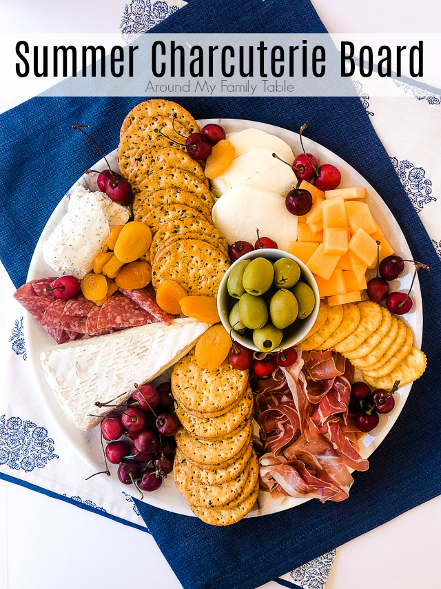 charcuterie board on a white platter with summer cherries, cantaloupe, meats & cheeses