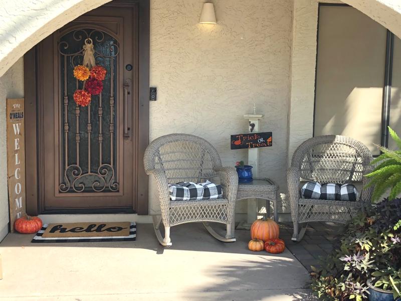 fall porch with pumpkins and buffalo check