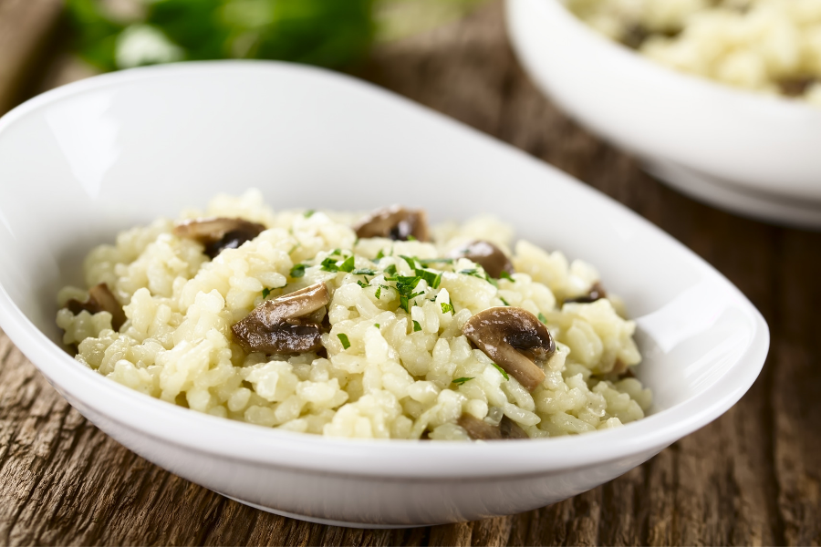 risotto in white bowl on wood table