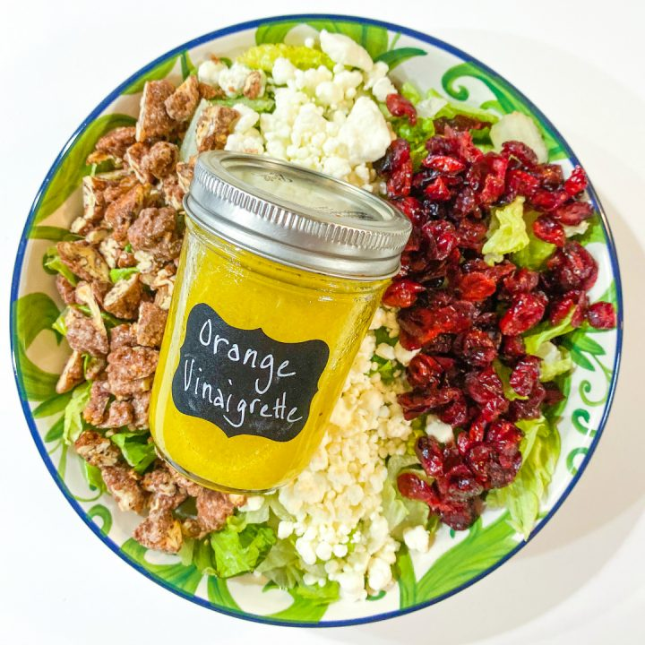 Cranberry, Goat Cheese, & Pecan Salad with Orange Vinaigrette in a bowl with a jar of dressing