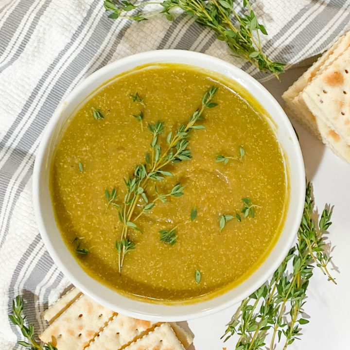split pea soup in white bowl with thyme