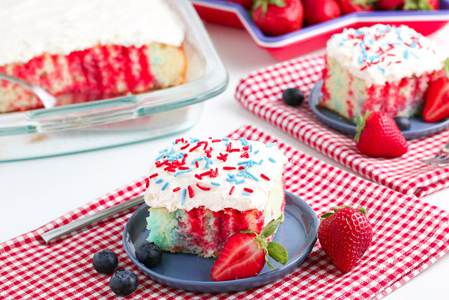 4th of July Poke Cake with berries on a white table with red checkered napkins