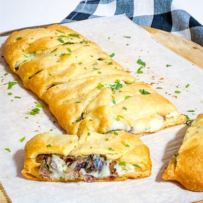 Steak & Provolone Crescent Braid on parchment paper on a pizza peel