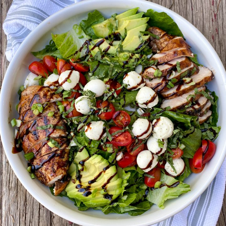 Italian Grilled Chicken Salad on a wood table with a white and blue towel