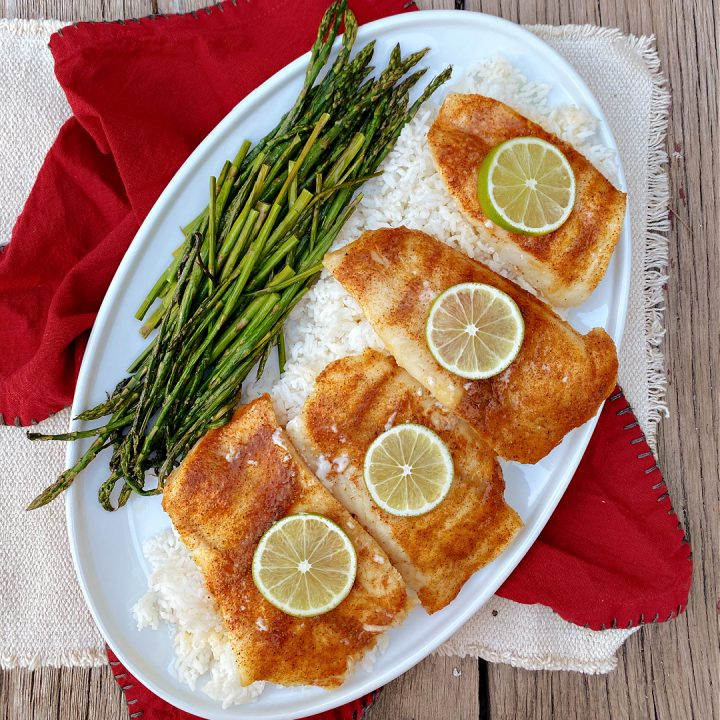 Cajun Oven Baked Cod on a plate with rice and asparagus